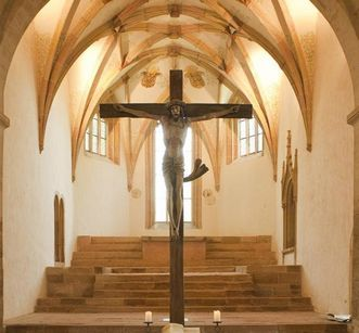 View in the choir room of Lorch Monastery church with a crucifix in the foreground. Image: Roland Schwarz